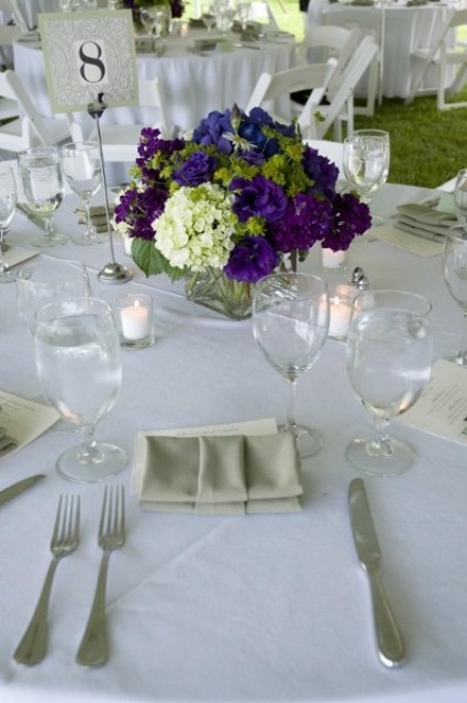 a deep purple and white floral wedding centerpiece surrounded by candles will bring much color