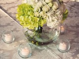 neutral blooms paired with bright green ones and surrounded with candles for a spring wedding