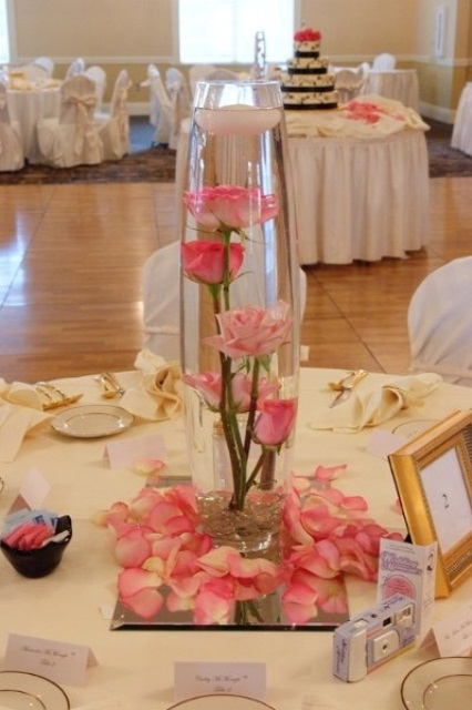 a pink wedding centerpiece of pink roses in a vase and on a mirror plus petals all around