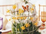 a whimsy cage spring wedding centerpiece with yellow blooms, grass, butterflies and a cage