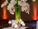 a tall vase with white orchids and callas surrounded with candles is a refined and chic idea for a spring wedding
