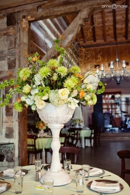 a green and peachy floral centerpiece in a tall urn is great for a spring wedding