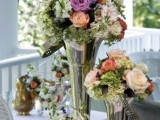 whimsy floral wedding centerpieces of silver vases with peachy, blush and purple blooms and greenery