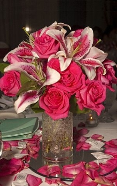 a fuchsia-colored lily and rose wedding centerpiece is super bright and statement-like