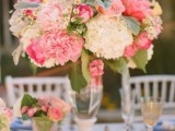 a pink and blush wedding centerpiece with neutral blooms and foliage looks very chic and very cool