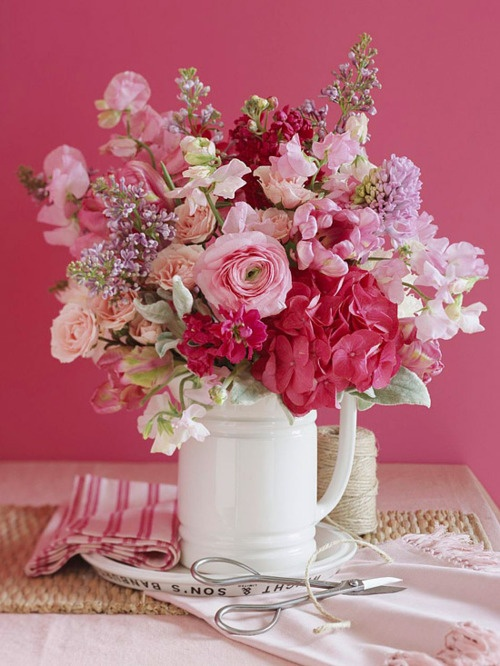 a bright and beautiful red, pink and lilac wedding centerpiece for a spring wedding