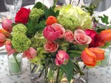 a pink, red, orange and green floral and greenery wedding centerpiece is great to bring much color to the table