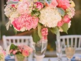 a tall pink and white floral centerpiece with foliage is a bright and cool idea for a spring wedding