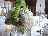 a white floral wedding centerpiece with some greenery and a couple of mauve blooms that make the arrangement look cool