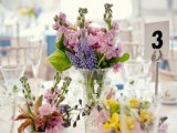 a pink, lilac and yellow floral wedding centerpiece with some foliage is a cool idea for spring or summer