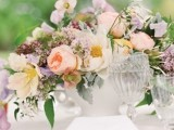 a pastel wedding centerpiece in peachy, lilac, light pink and some greenery for a spring wedding