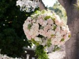 a tall topiary wedding centerpiece in light pink and greenery is a gorgeous idea for a spring wedding