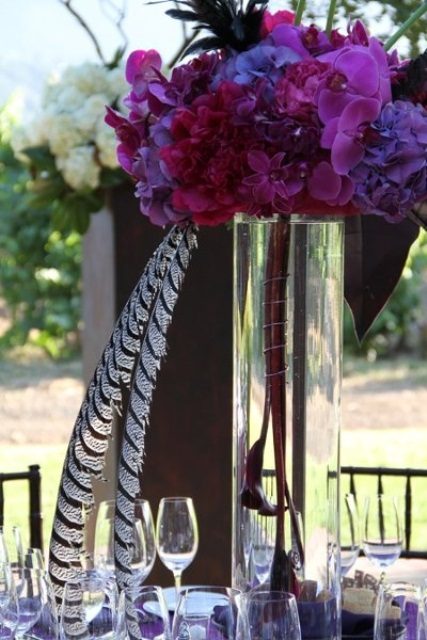 a tall purple and pink floral centerpiece in a clear tall vase is great for a bright spring wedding