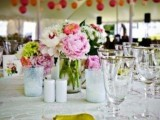 a pink and neutral floral wedding centerpiece with some greenery is a bold and chic idea to try