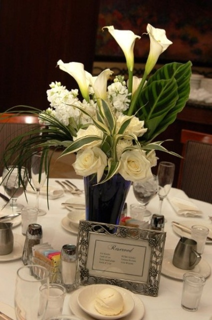 a white floral spring wedding centerpiece with foliage is a cool idea for a fresh spring wedding