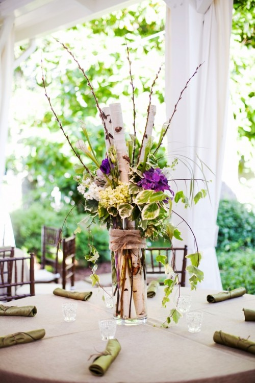 a greenery, twig and branch wedding centerpiece with a touch of purple blooms and burlap for a rustic spring wedding