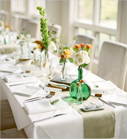 an exquisite spring wedding tablescape with neutral linens and a green runner, bold and white blooms and greenery, silver cutlery and vintage books