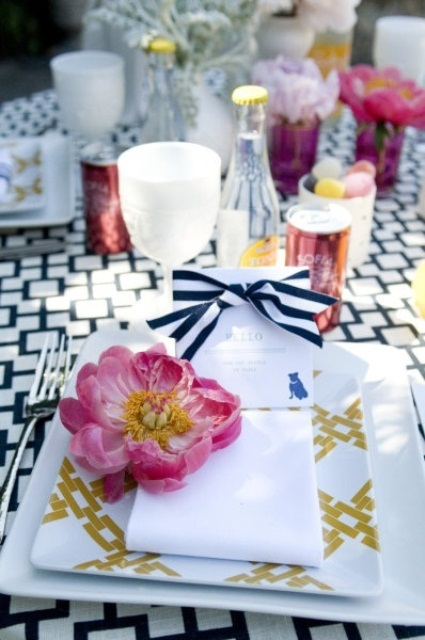 a vivacious spring wedding table with a printed tablecloth, plates and ribbons, bright pink blooms and white square chargers