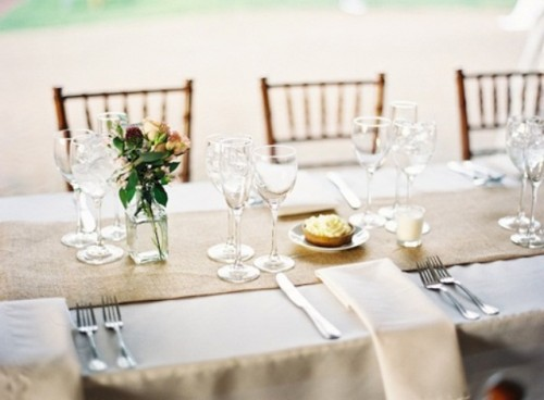 a neutral spring wedding table setting with a burlap runner, some pastel blooms in a bottle and candles plus refined glasses