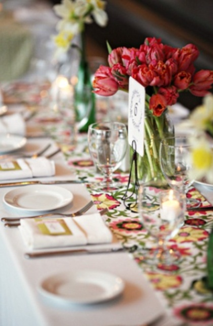 a bold wedding tablescape with a floral runner, bold red and neutral blooms, candles and neutral porcelain is fun and bright