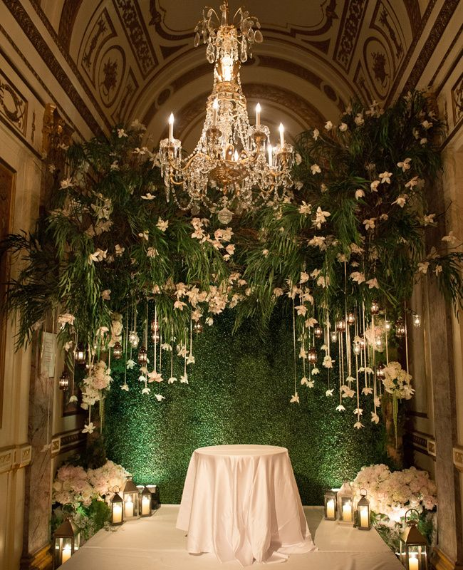 a greenery backdrop with greenery and white blooms hanging down and a chandelier for a sophisticated wedding
