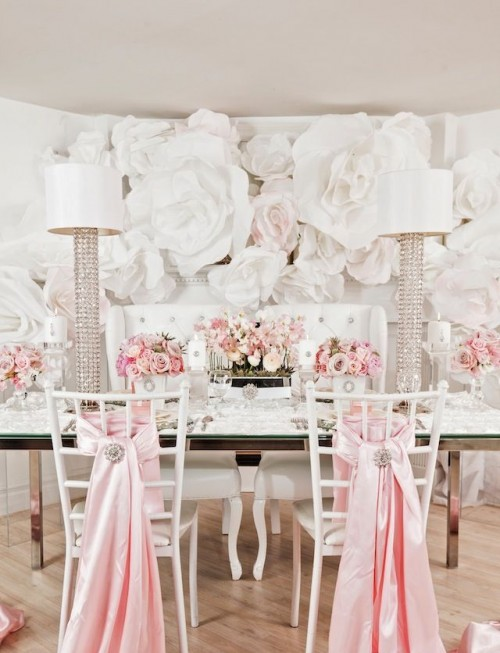 oversized white paper blooms on the wall make the backdrop fantastic, bold and catchy