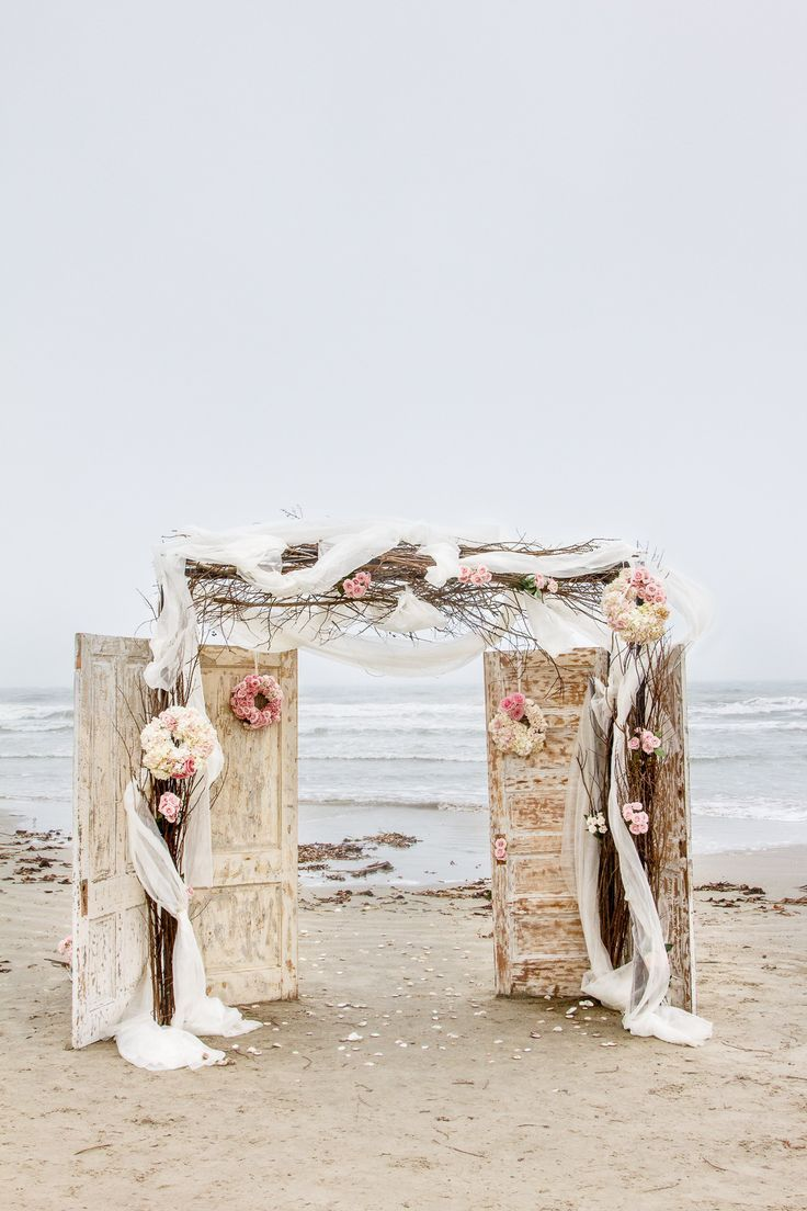vintage doors, blooms, neutral fabric and branches make up a chic and refined wedding backdrop