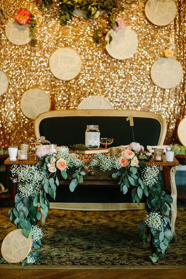 a gold sequin reception backdrop with hoops with newspapers is a fun and creative backdrop idea