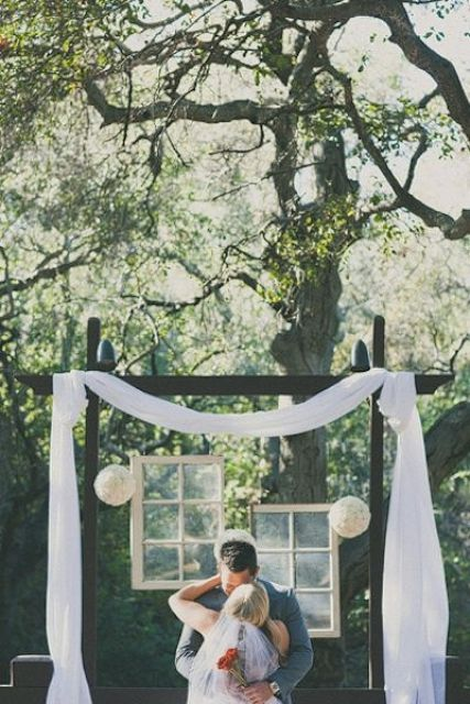 a unique wedding backdrop of dark stained wood, fabric, paper balls and vintage windows hanging