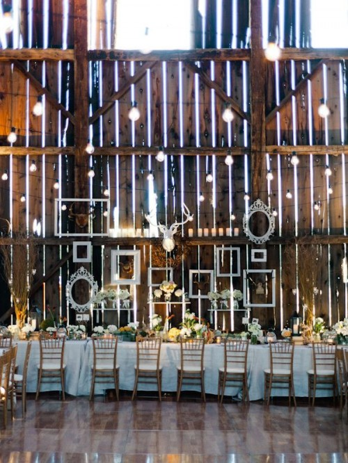 a pallet wall with white frames attached to it and lots of lights is a stylish idea for a vintage rustic wedding