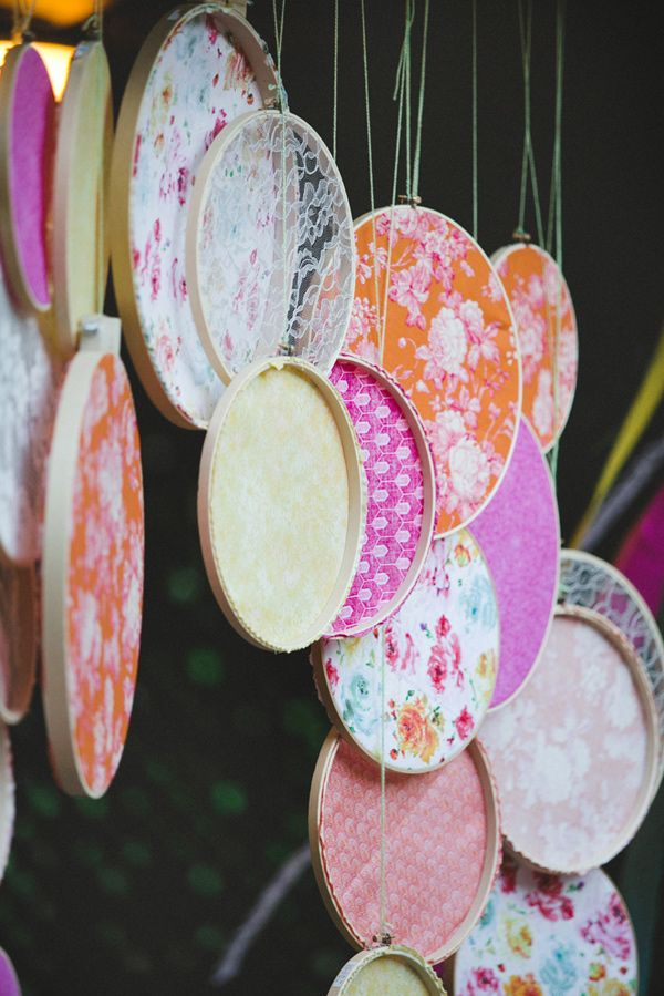 hoops with colorful fabric and lace make up a fun and bright reception or wedding backdrop