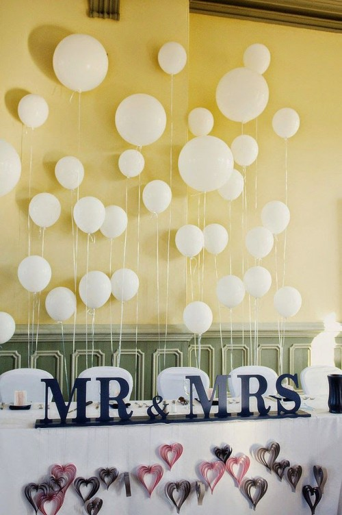 white balloons attached to the wall is a fun and whimsical party-inspired idea of a reception backdrop