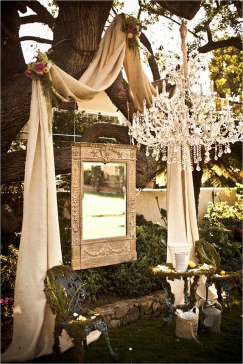 a unique wedding backdrop idea with fabric, a mirror, blooms and a crystal chandelier