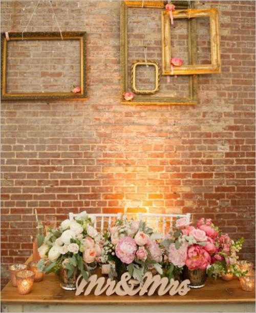 gold frames attached to the wall with pink blooms is a refined and chic decor idea for most of weddings