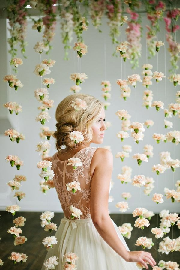 threads with carnations hanging down make up a cool wedding backdrop with a strong romantic feel