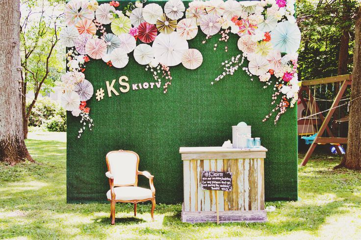 a green backdrop with colorful paper fans, a refined chair and a wooden bar with drinks and props