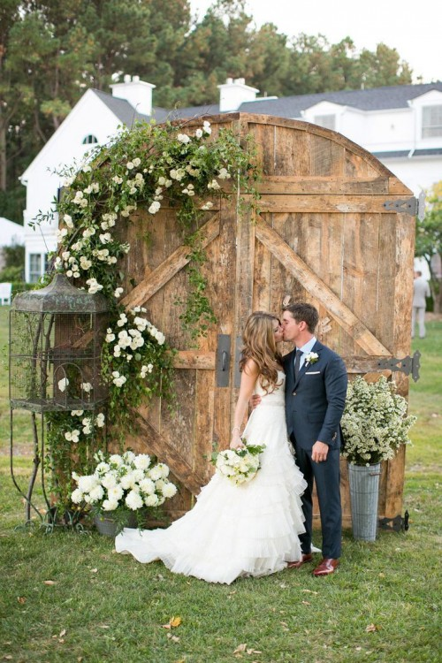 old barn doors with greenery and white blooms, a cage and a bucket with blooms is a chic wedding backdrop