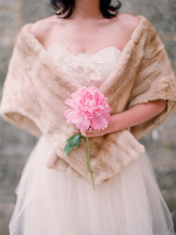 a chic A line strapless wedding dress with a petal bodice and a beige faux fur cover up is ideal for a fall or winter wedding
