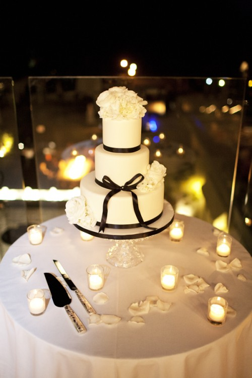a white wedding cake decorated with black ribbones, bows and topped with white blooms