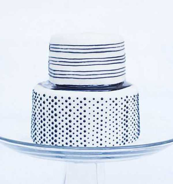 a white wedding cake decorated with black stripes and polka dots is a cool and fresh option