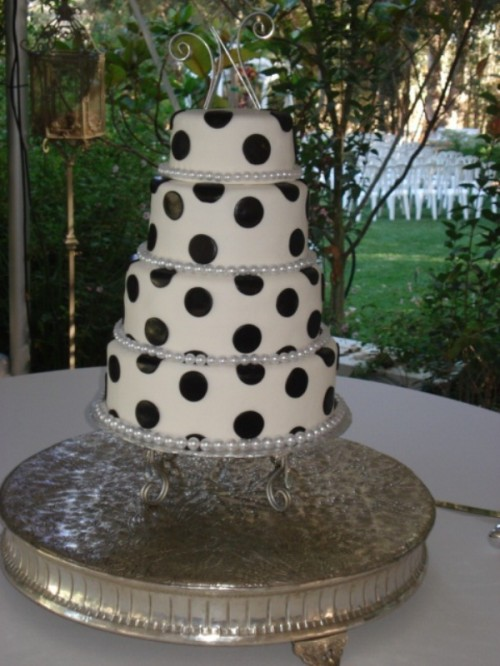 a white wedding cake decorated with oversized black polak dots and a shiny and sparkling topper