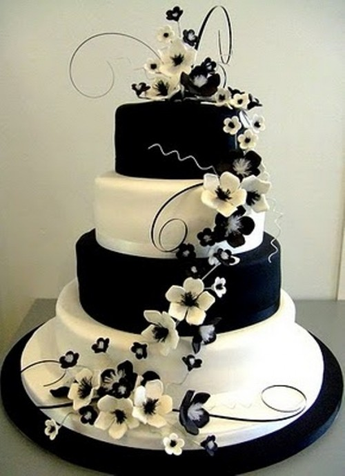a large wedding cake with black and white tiers and sugar flowers in blakc and white is a sophisticated wedding cake