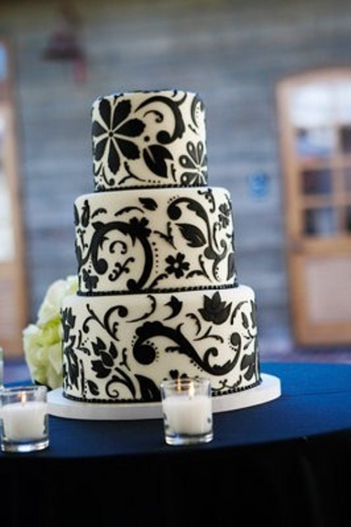a white wedding cake decorated with elegant and chic black floral patterns all over looks very pretty