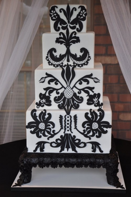 a white wedding cake decorated with unusual black patterns will fit a folksy wedding