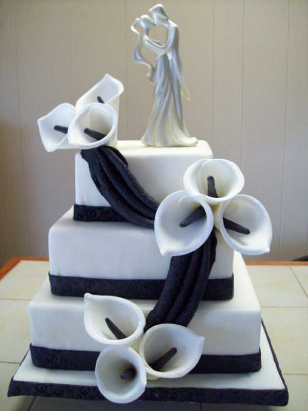 a white square wedding cake decorated with black ribbons, sugar callas and a topper
