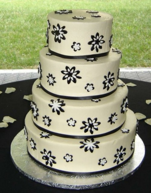 a white wedding cake decorated with black and white blooms and black ribbons