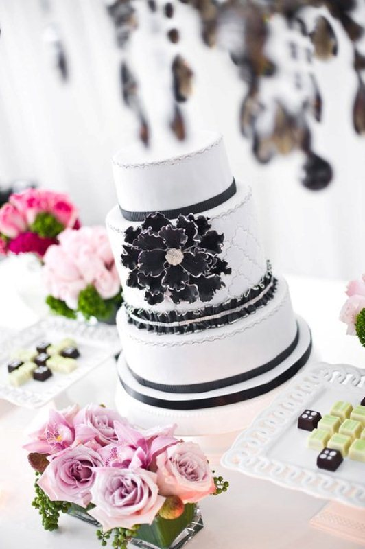 a black and white wedding cake with patterns and silver decor plus an oversized sugar bloom