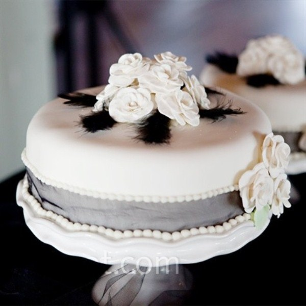 a white wedding cake with grey ribbon, sugar blooms and black feathers is a bold and cool idea