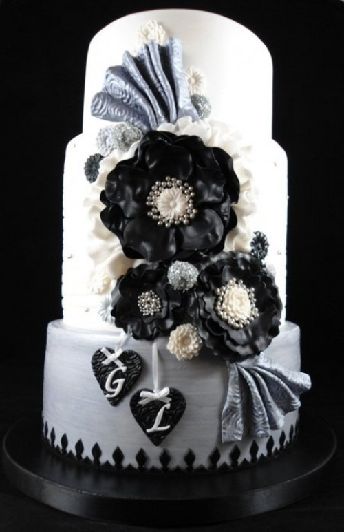 a white wedding cake decorated with black and grey sugar blooms, bows, hearts and beads