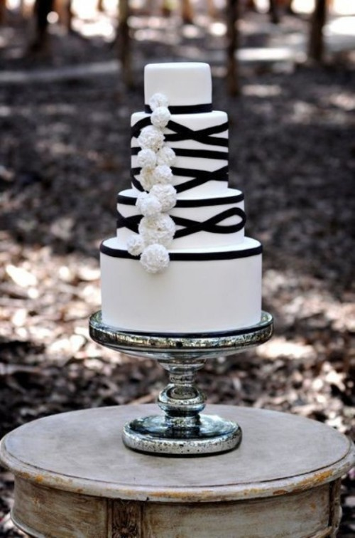 a white wedding cake decorated with black ribbons and white fluffies for a cool and bold look
